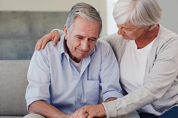 eine Frau tröstet einen älteren Mann